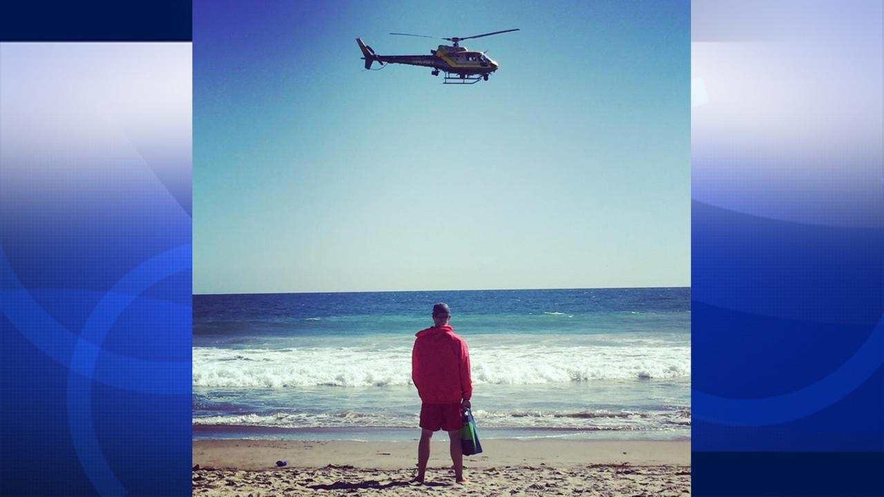 A Los Angeles County Sheriffs Department helicopter flies in search of a missing swimmer in Zuma Beach on Sunday, July 12, 2015.