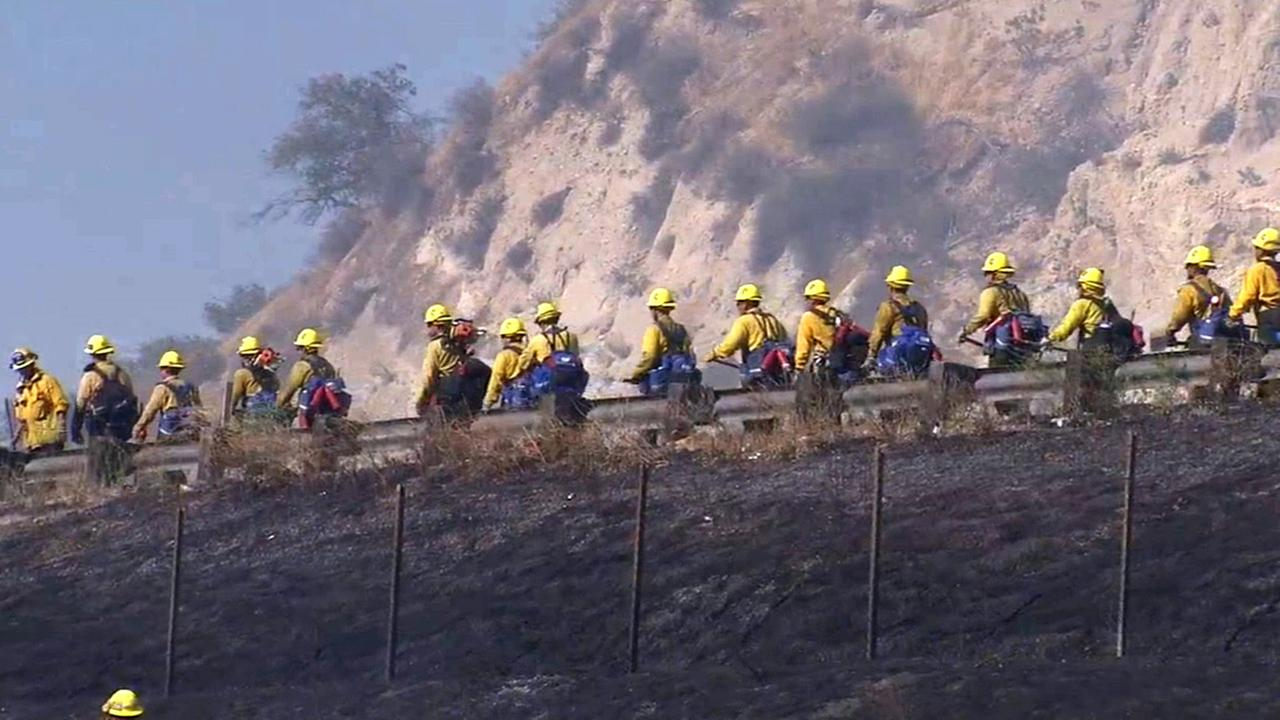 Firefighters respond to a brush fire burning along the 14 Freeway near the 5 Freeway in Newhall on Sunday, July 12, 2015.