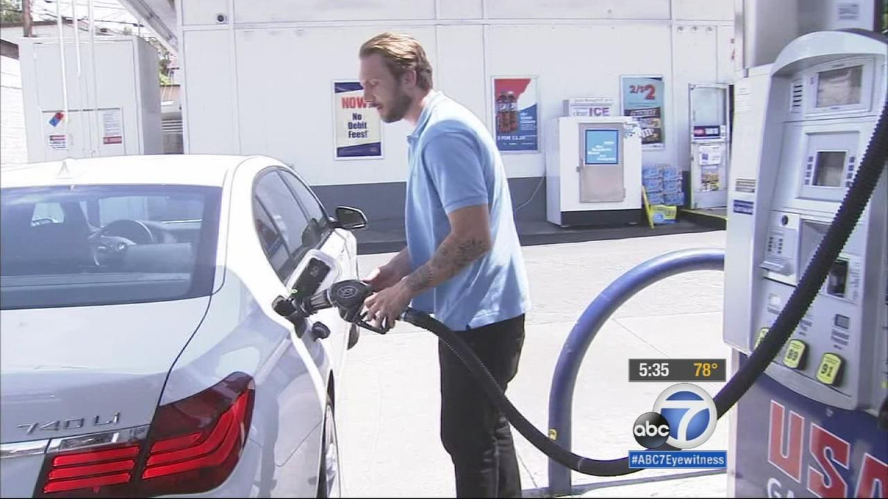 A man pumping gas at a gas station is shown in an undated file photo.