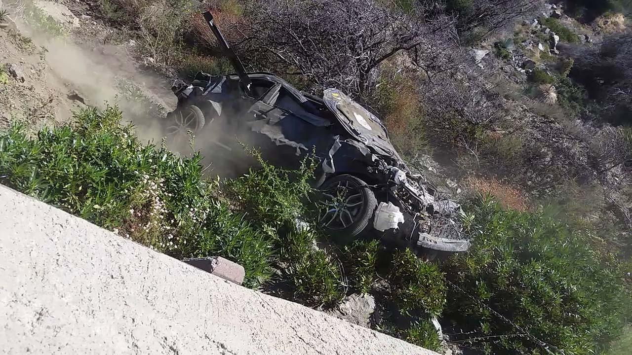 A tow truck pulls a car that rolled over back onto the Angeles Crest Highway on Sunday, Aug. 9, 2015.