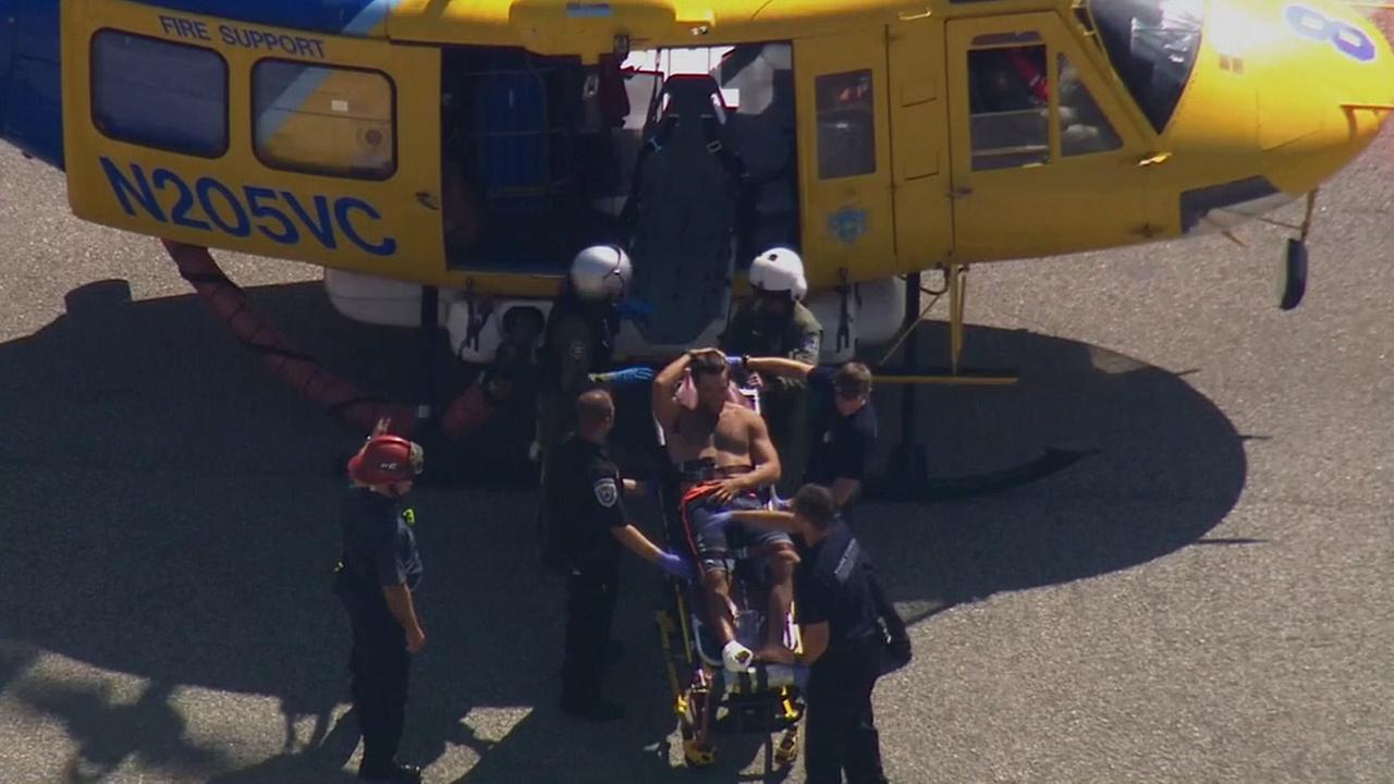 Medical personnel work to get a man bitten by a shark into a helicopter to airlift him to a hospital on Saturday, Sept. 5, 2015.