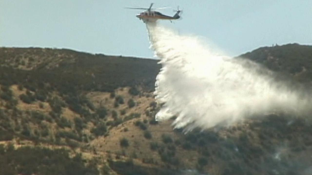 A helicopter drops water on a brush fire in Lancaster on Saturday, Sept. 5, 2015.