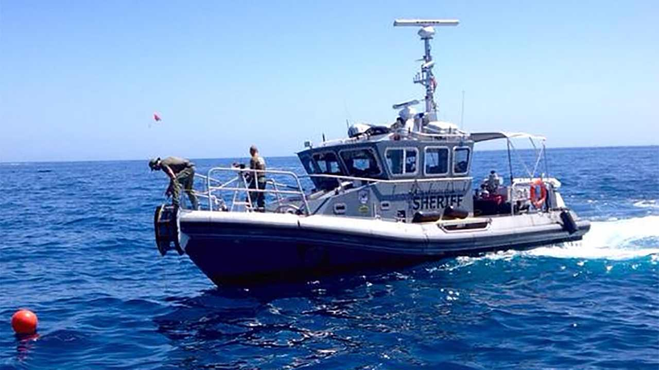 Rescue crews dive off a Los Angeles County Sheriffs Department boat in search of a missing boater off the coast of Catalina Island on Sunday, Sept. 6, 2015.