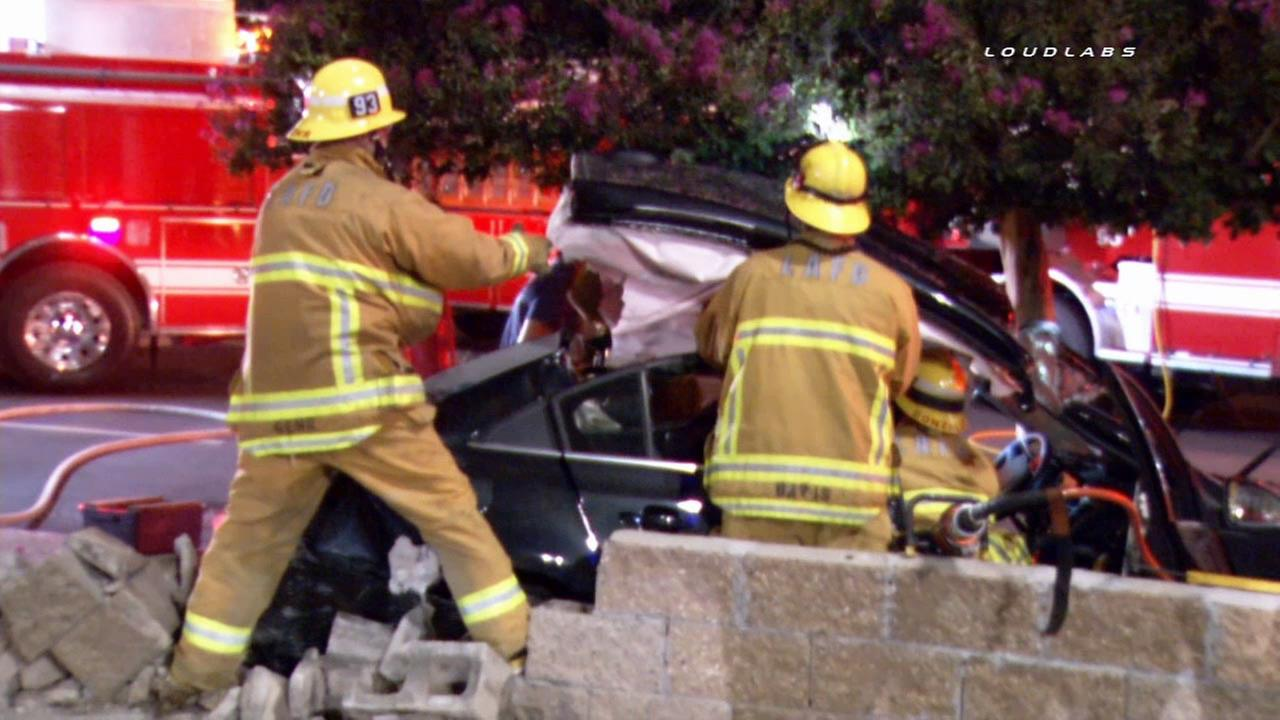 Emergency crews work to help a woman trapped in her car following a crash in Encino on Sunday, Sept. 20, 2015.