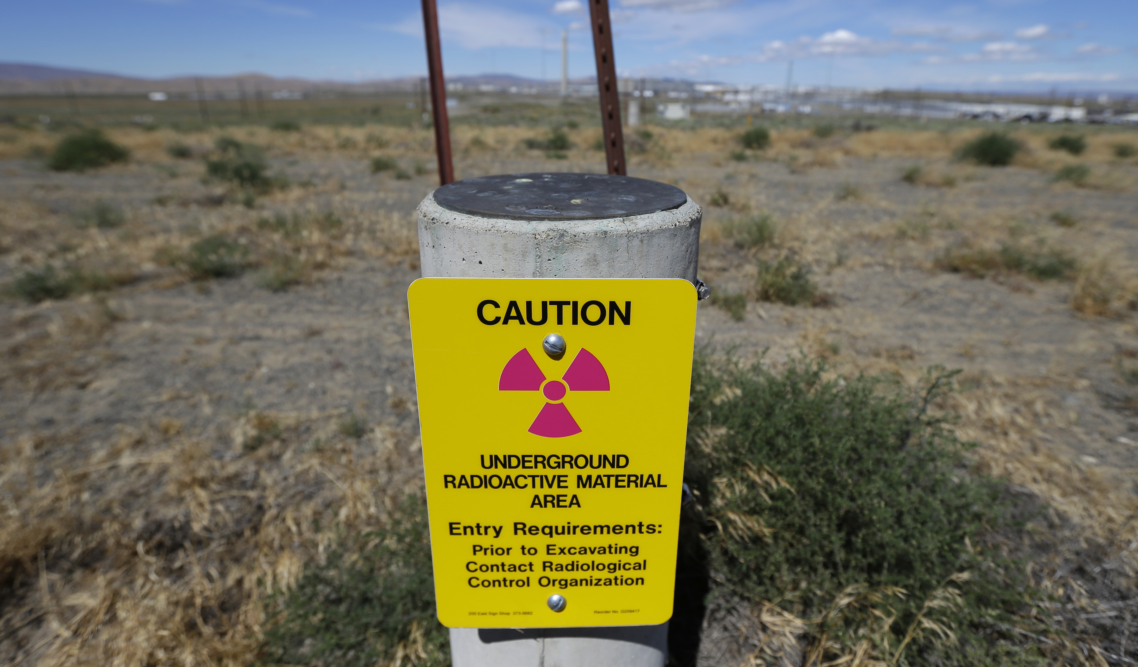 FILE - In this photo taken July 11, 2016, a sign warns of radioactive material stored underground on the Hanford Nuclear Reservation near Richland, Wash.