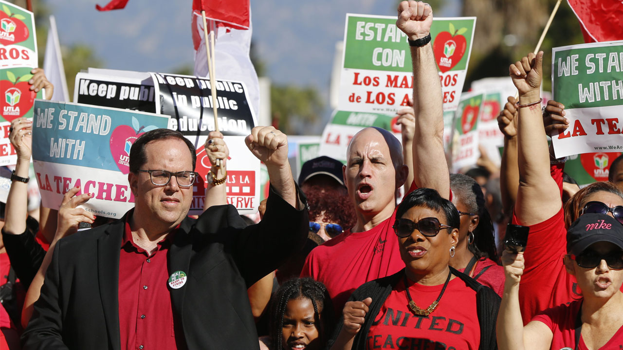 In this Dec. 15, 2018, photo, United Teachers Los Angeles, UTLA president, Alex Caputo-Pearl, left, joins teachers at a rally next in downtown Los Angeles.