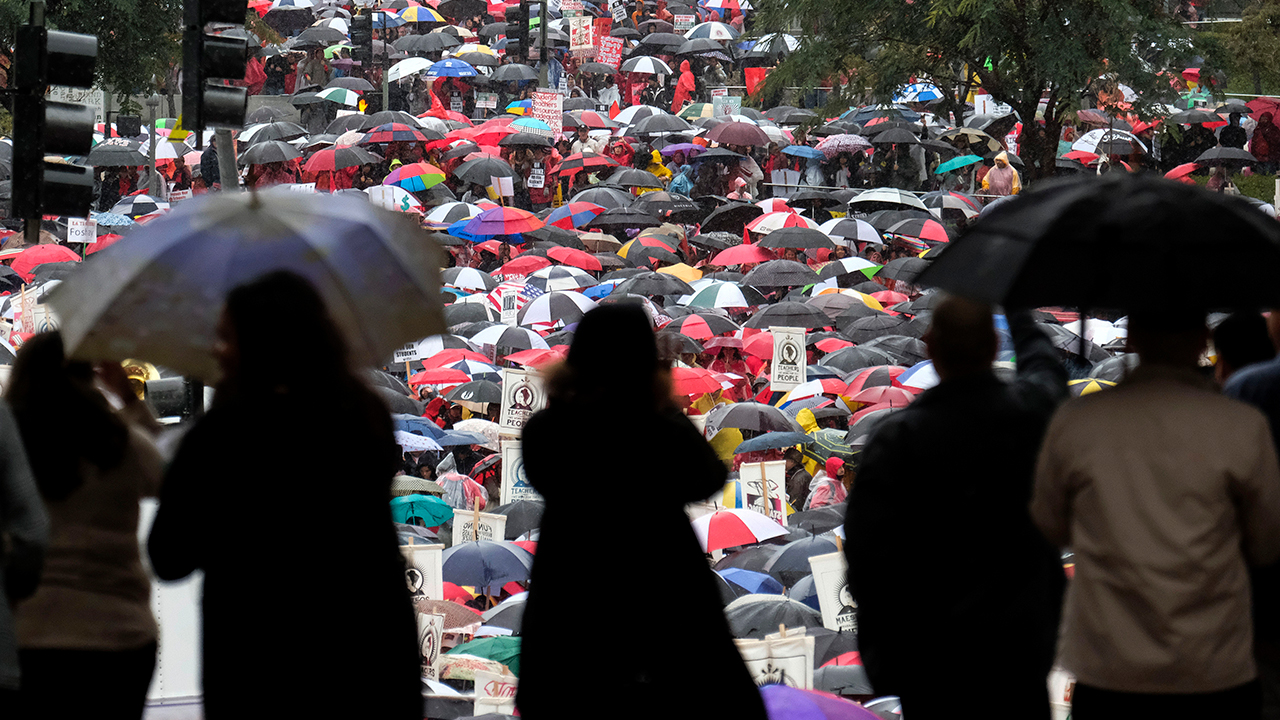 Thousands of teachers and supporters hold signs in the rain during a rally Monday, Jan. 14, 2019, in Los Angeles.