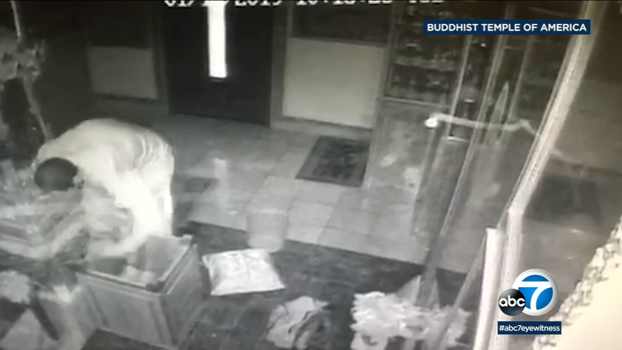 A surveillance image shows a suspect breaking into a wooden donation box at a Buddhist temple in Montclair.