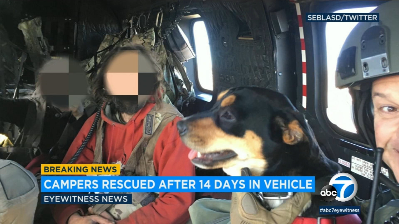 Two people and two dogs were rescued from the mountains northwest of Castaic after being snowed in their vehicle for 14 days, officials said.
