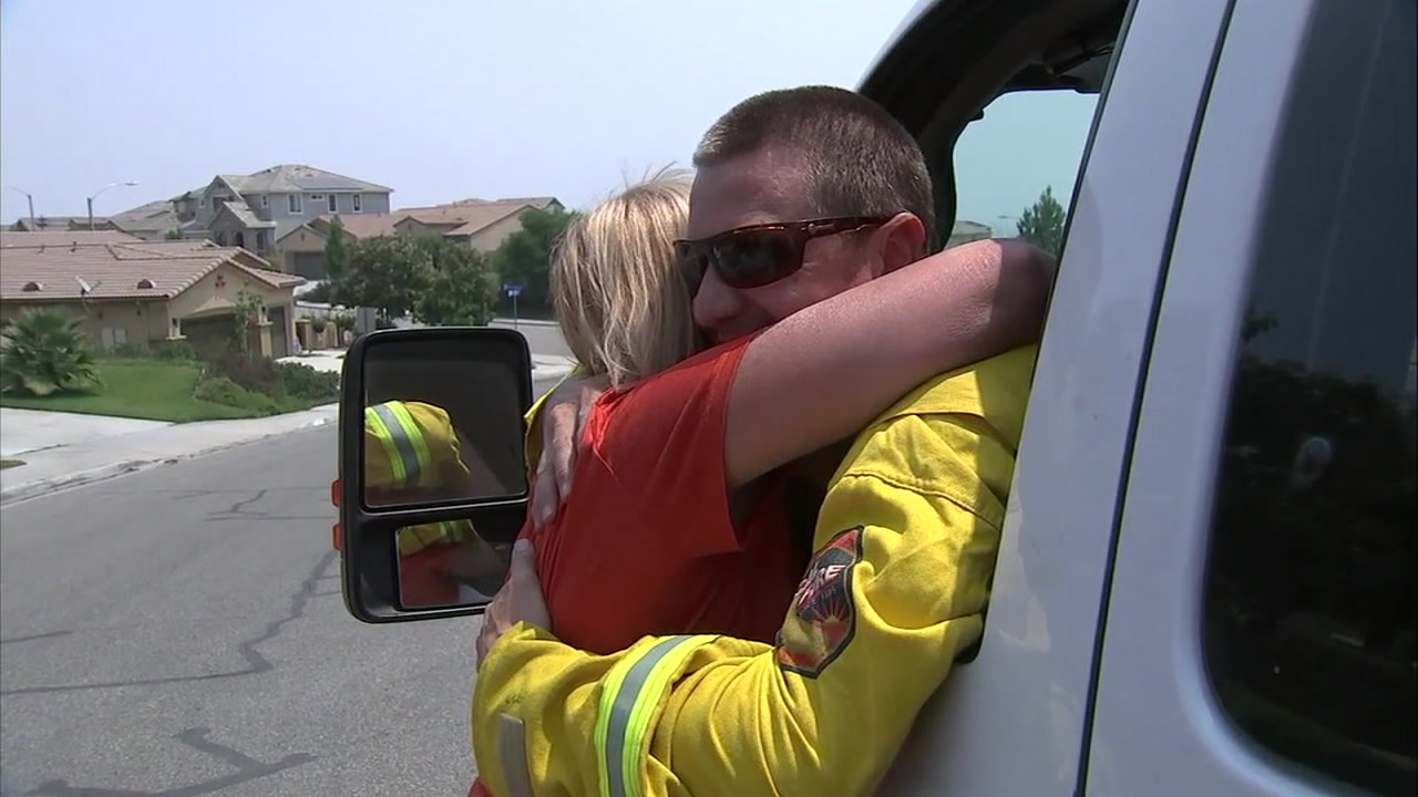 A Holy Fire evacuee hugs a firefighter after her Lake Elsinore home was saved from the flames.