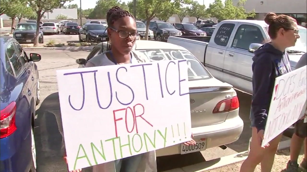 A woman holds a sign saying Justice for Anthony in front of the L.A. County Department of Children and Family Services office in Lancaster.