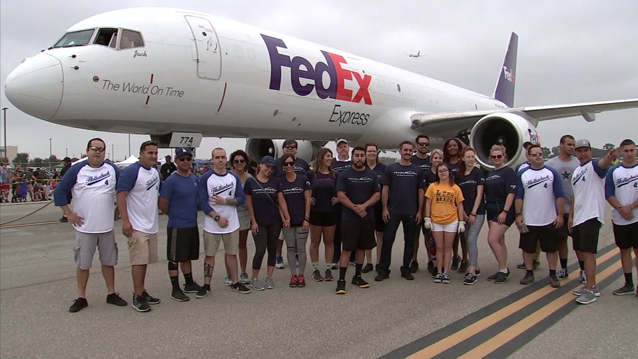 Teams pose in front of a FedEx cargo plane at the Long Beach Airport after competing to see who could pull it 12 feet the fastest.