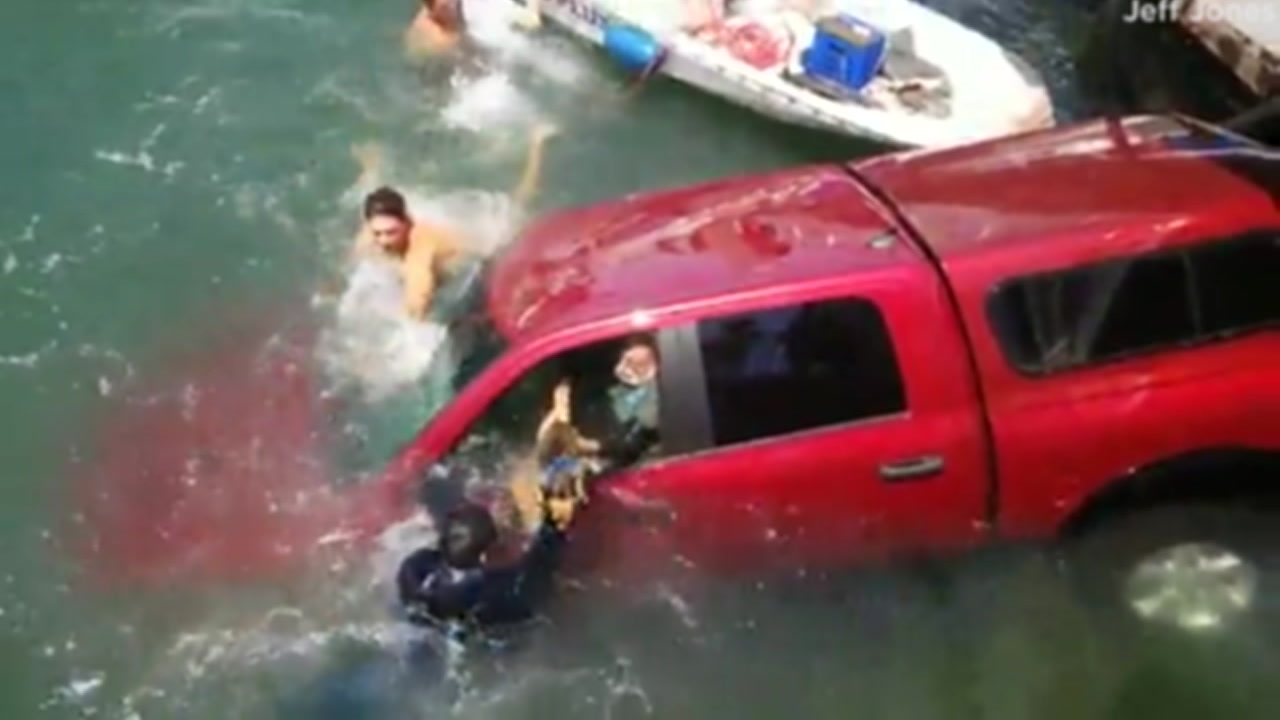 Good Samaritans are seen rescuing a man, woman and a dog from a submerged car in Long Beach.