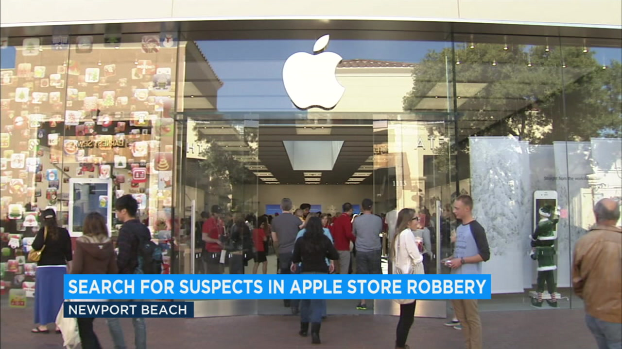 People stand outside an Apple Store in Newport Beach after a heist of 38 iPhones on Tuesday, Aug. 21, 2018.