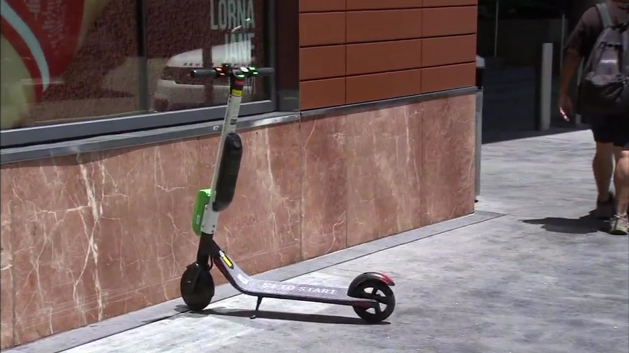 A rental scooter is shown in front of a business in a city in Los Angeles County.