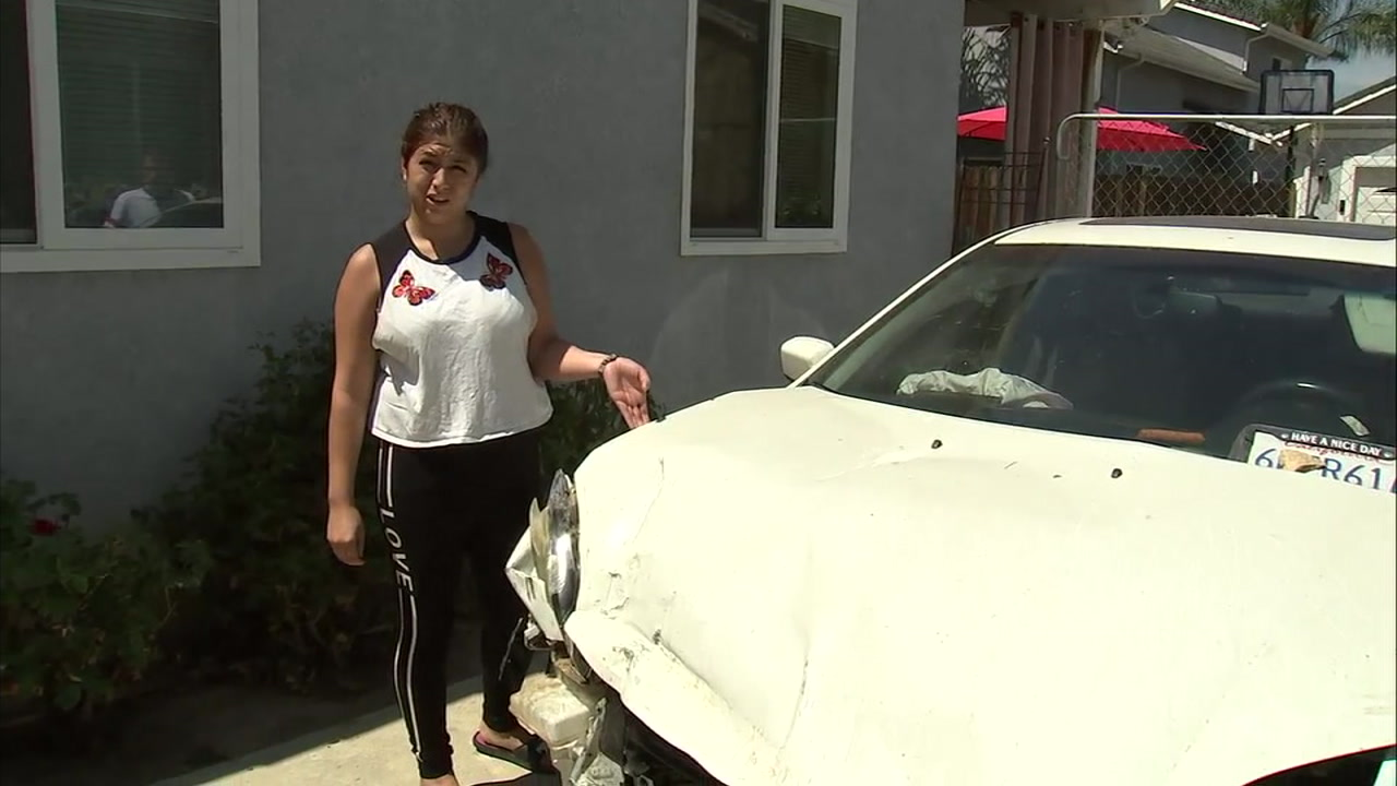 Michelle Monge is shown pointing to the damage to her vehicle after a rock fell on it while she and her boyfriend were traveling on Malibu Canyon Road.