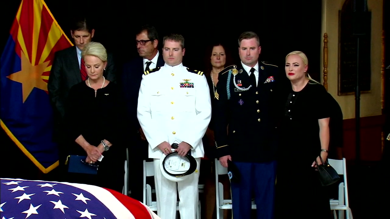 Sen. John McCains flag-draped casket is shown off to the side as his family hold hands to honor him during a public service in Arizona.
