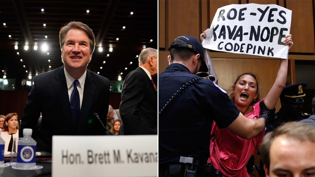 A woman stands and voices her opposition to Supreme Court nominee Brett Kavanaugh during a Senate Judiciary Committee confirmation hearing Tuesday, Sept. 4, 2018.