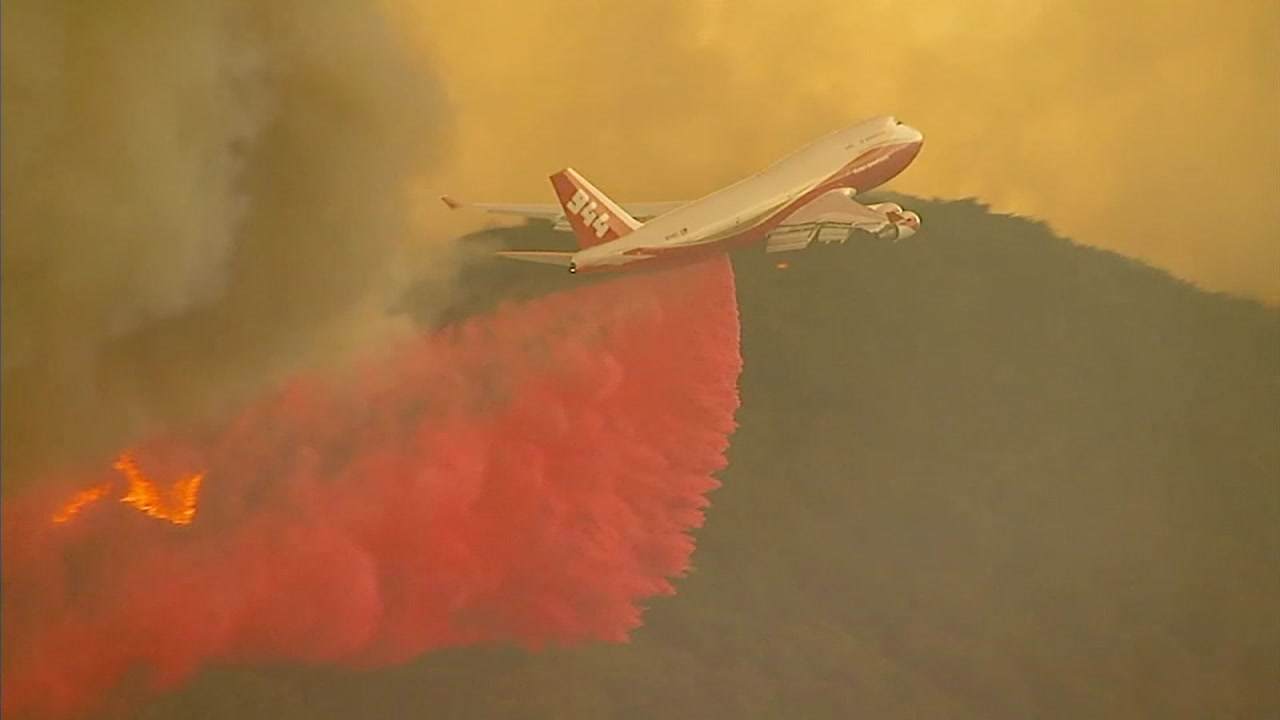 A plane drops fire retardant on areas about to be impacted by the Holy Fire while it was still raging in Orange and Riverside counties.