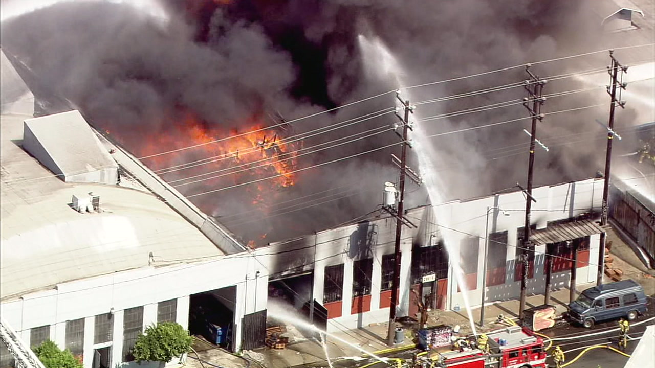 Three firefighters were injured while battling a massive blaze that erupted at a commercial building in the Boyle Heights area on Wednesday.