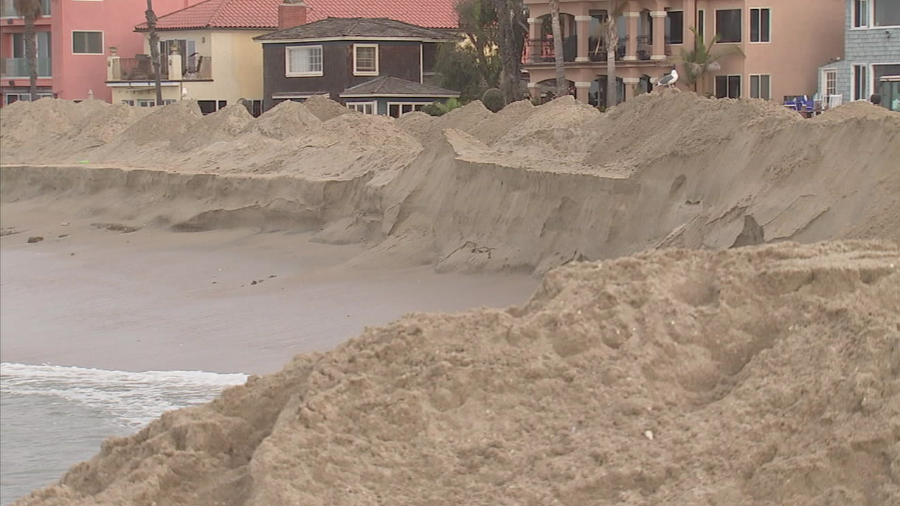 Crews with truckloads of sand are working to reinforce berms ahead of another expected surge in Long Beach.