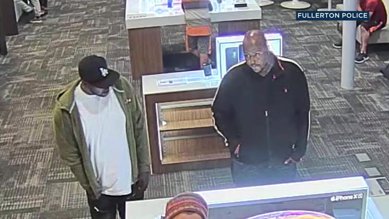 Two suspects are seen inside a wireless store in Fullerton on Monday, Oct. 8, 2018.
