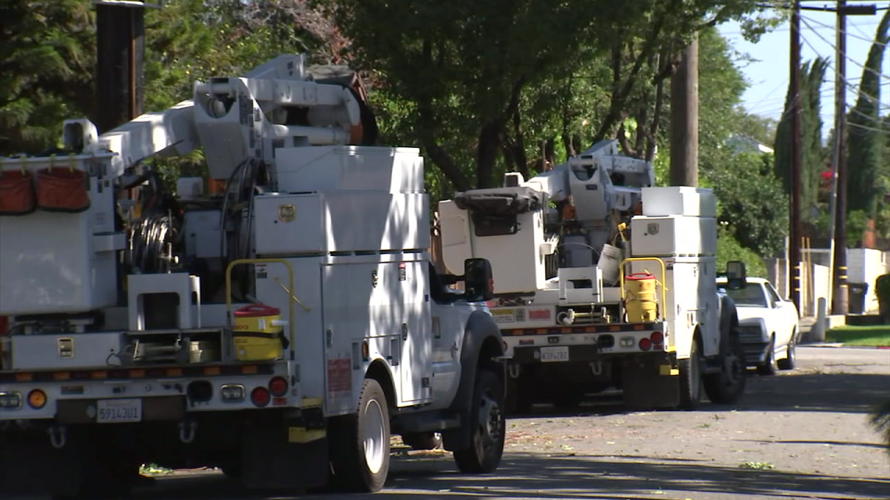 Power crews are shown near electrical power poles as they work to restore power after strong winds caused damage.