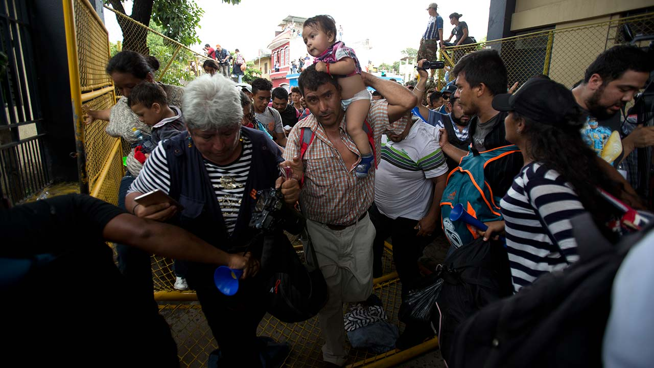 Migrants rush across the border toward Mexico, in Guatemala, Thursday, Oct. 18, 2018. They broke down the gates at the border and began streaming toward a bridge into Mexico.