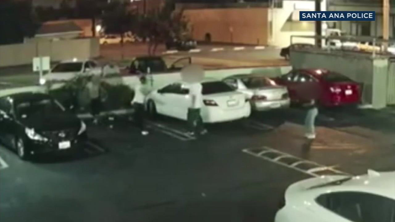 Surveillance video shows the moment a man in a white tank top shoots at his target, misses and hits a woman in the foot in Santa Ana.