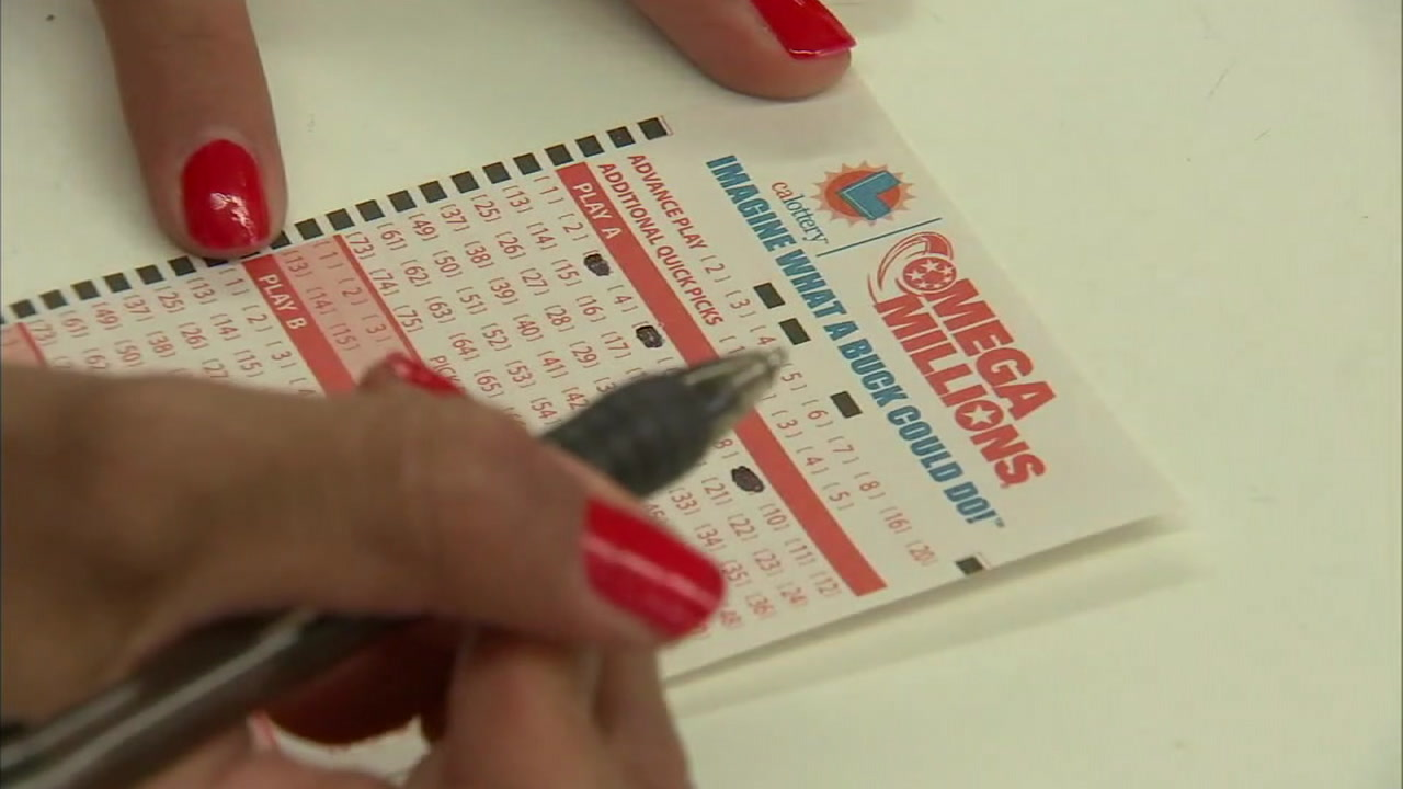 A woman is shown filling out her Mega Millions numbers before she buys her $2 ticket in the hopes of winning the massive jackpot.