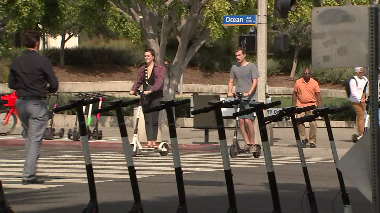 People riding scooters are shown going through a crosswalk in Santa Monica.