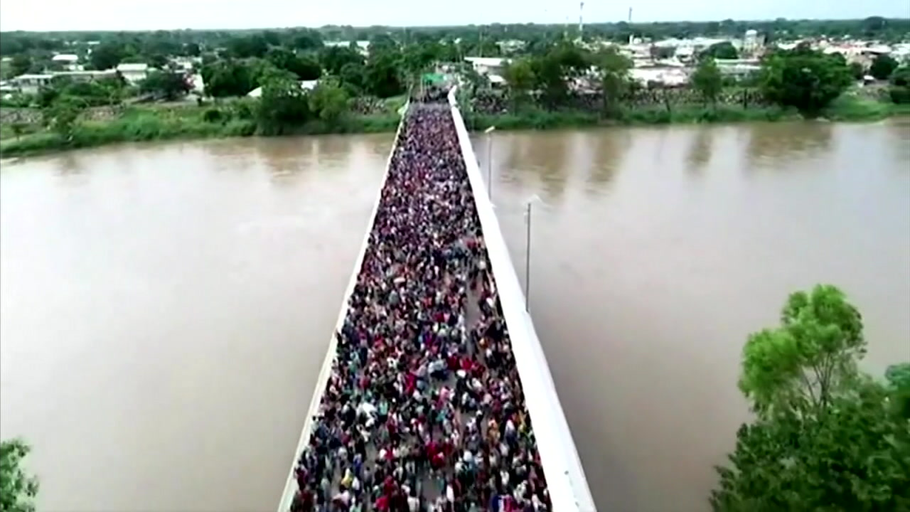 A caravan of migrants are seen crossing a bridge.
