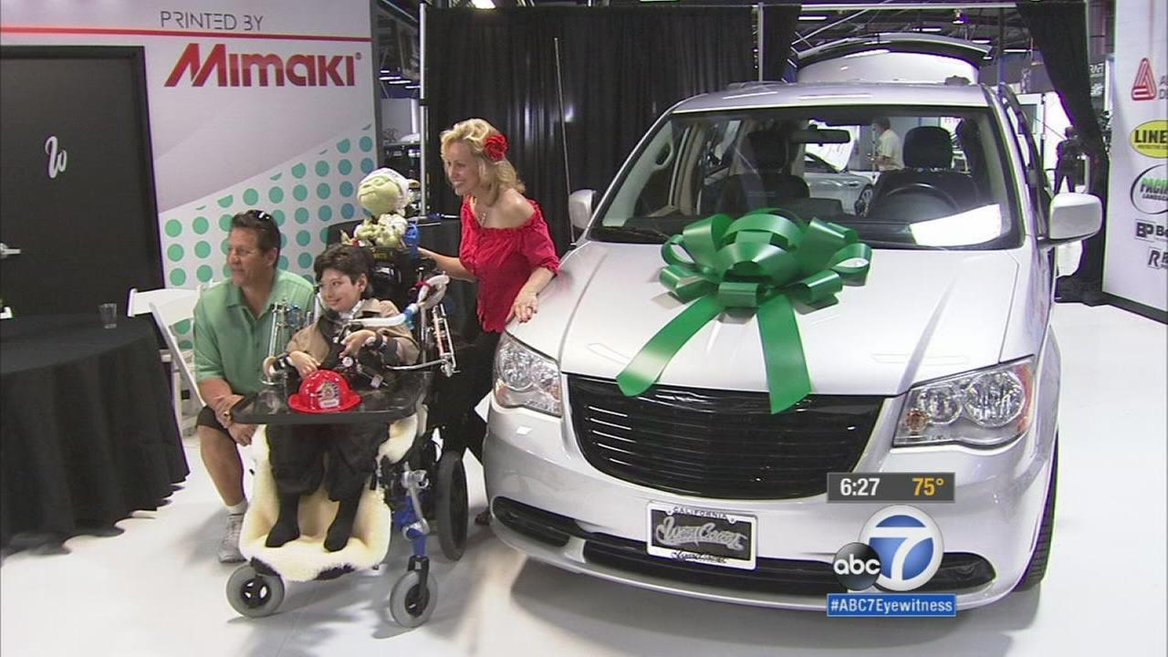 The Cumo family take photos with their new custom revamped Chrysler minivan donated to them by three Los Angeles-based businesses on Wednesday, Oct. 7, 2015.