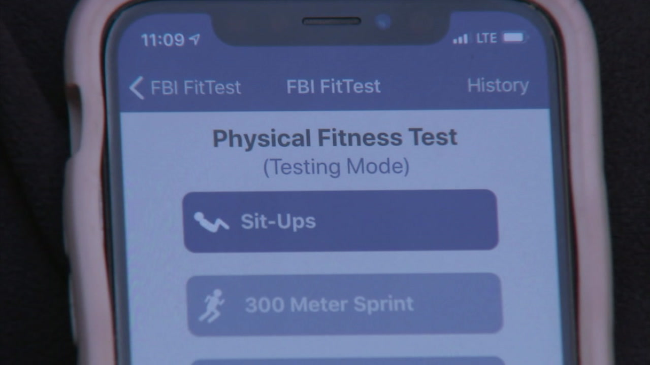 A phone screen shows the layout of the FBI FitTest mobile app, where users can test their physical fitness.