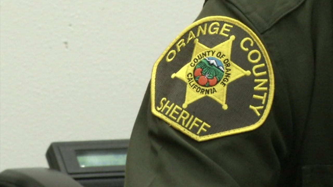 An Orange County Sheriffs Department badge is shown on a deputy.