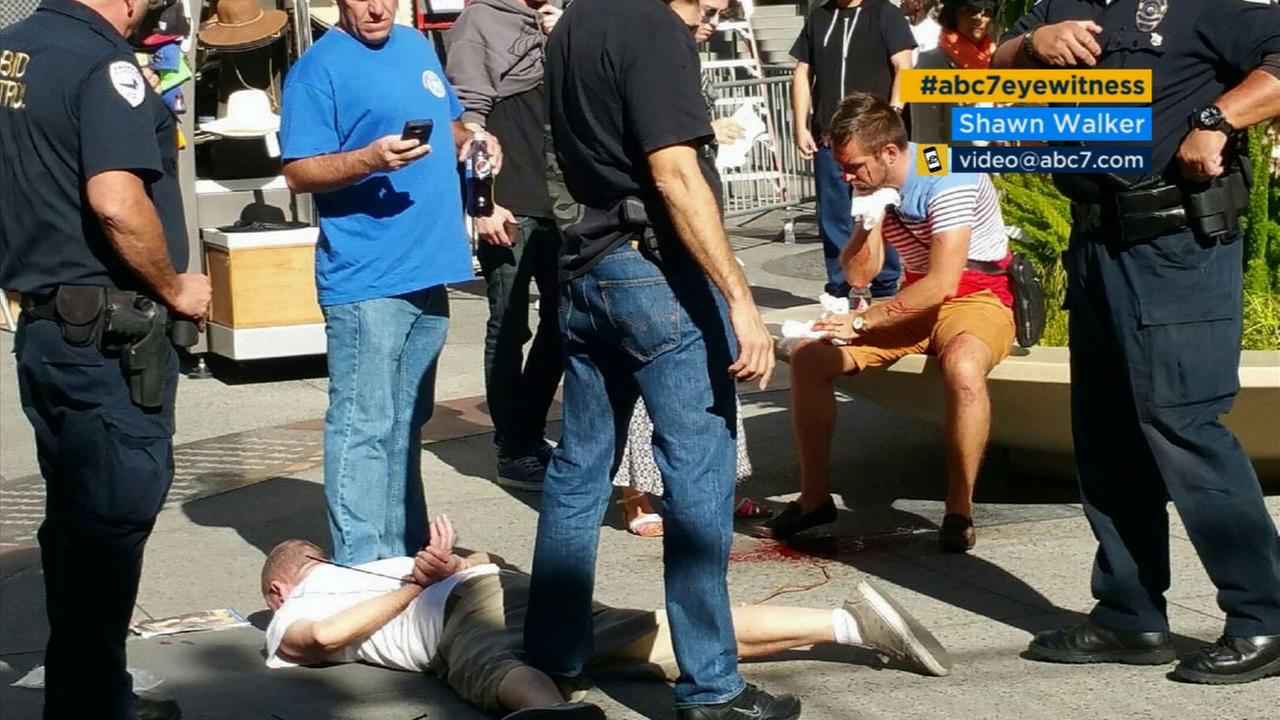 A stabbing suspect is taken into custody at Hollywood and Highland, as the victim waits to be transported to a hospital on Wednesday, Nov. 18, 2015.