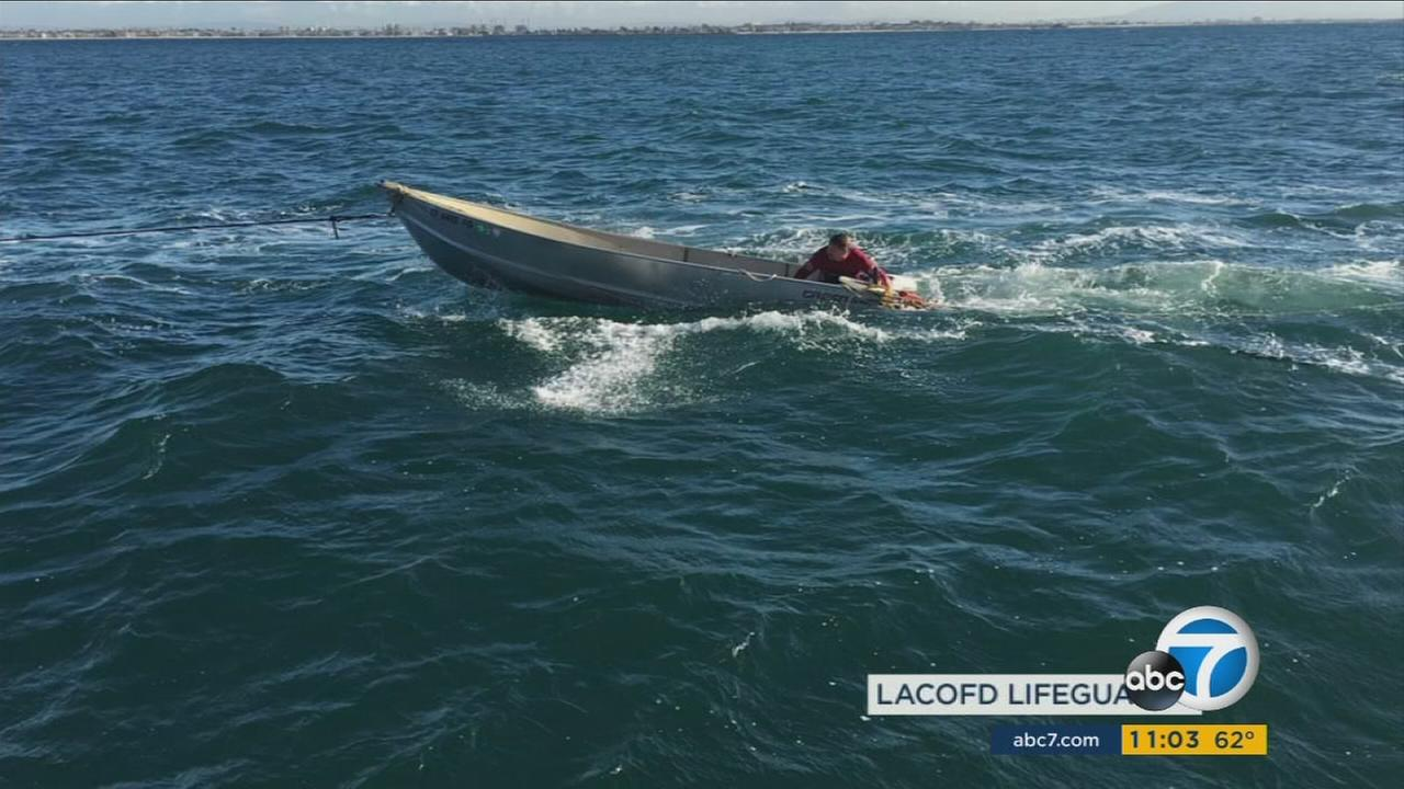 Four fishermen were rescued from the ocean off the Long Beach Harbor after their boat capsized amid big swells.
