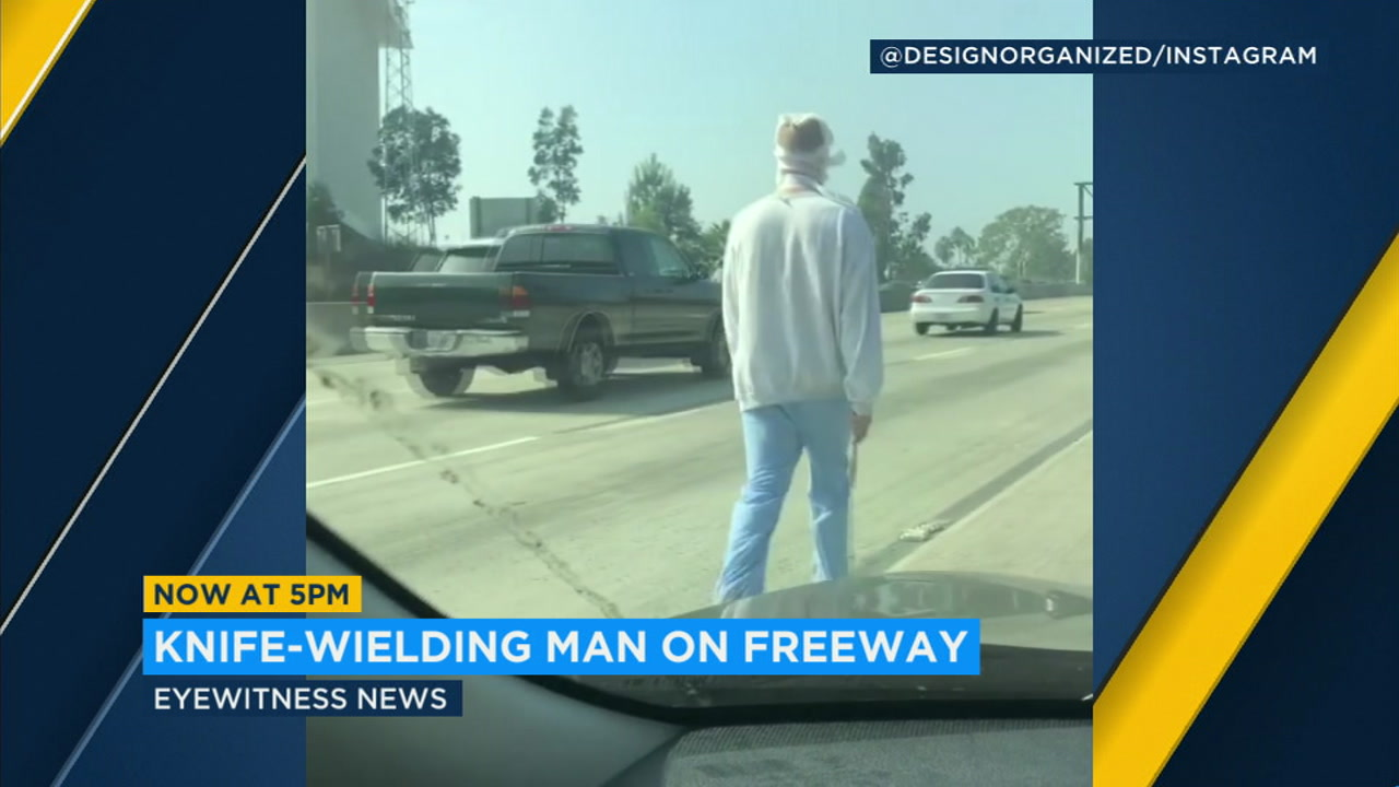 A knife-wielding man walks down the middle of the freeway wrapped in bandages in Los Angeles.