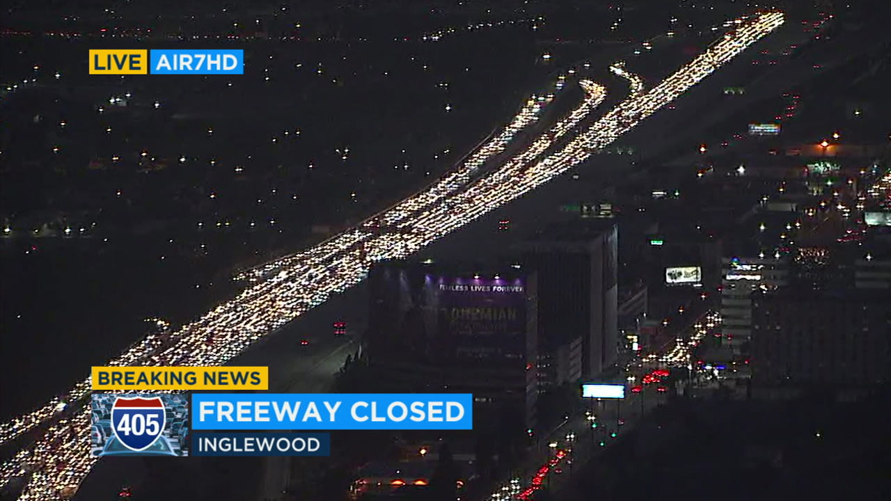 Traffic is backed up for miles in Inglewood after a woman threatens to jump from an overpass above the 405 Freeway.