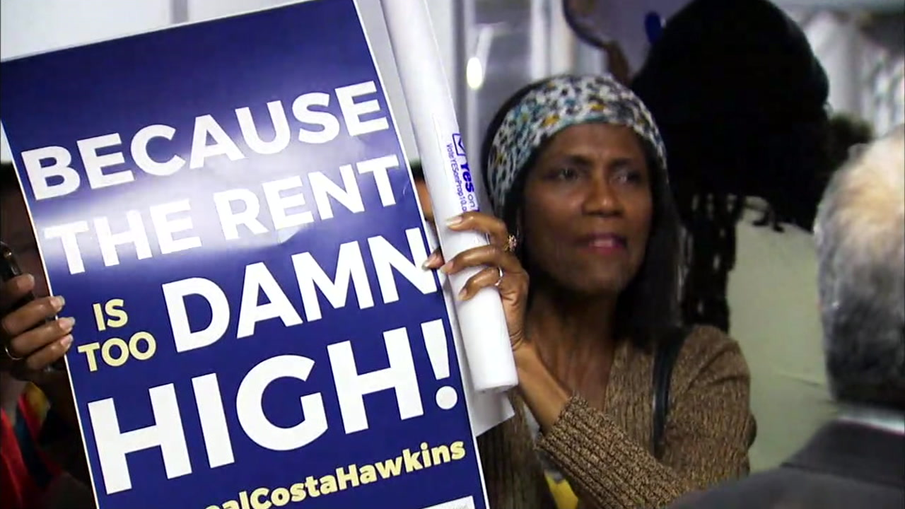 A woman holding a sign regarding high rents in Los Angeles and California is shown during a rally in Santa Monica.