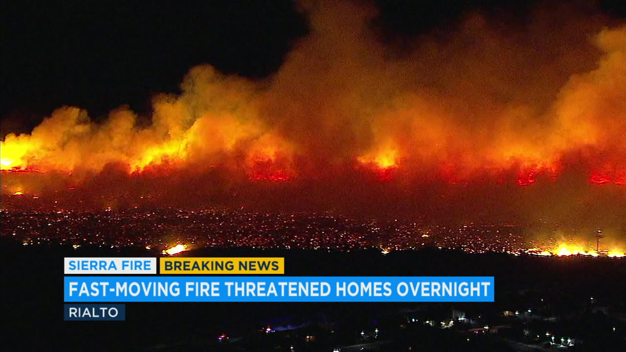 Flames from the Sierra Fire are seen in the Rialto area.