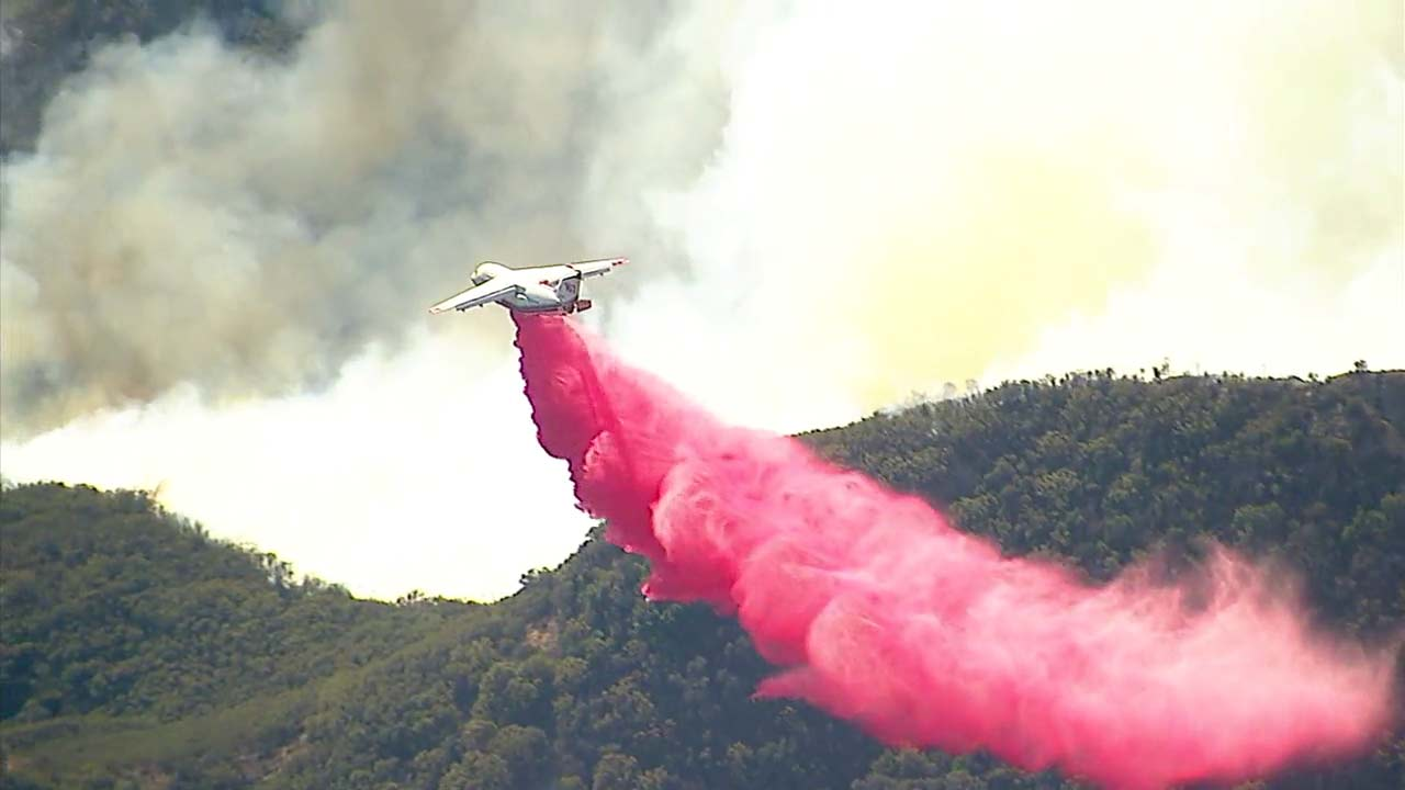 A plane drops fire retardant on the Woolsey Fire.