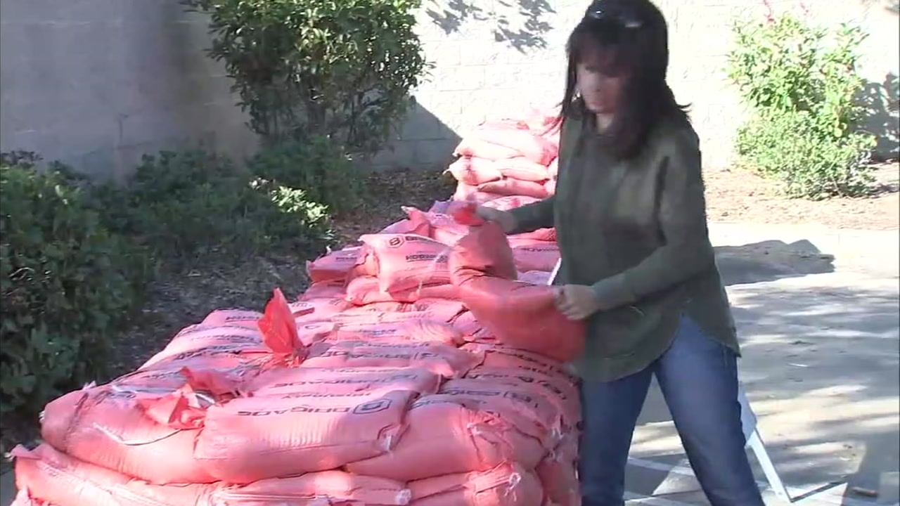 A woman grabs sandbags in preparation for rain coming into the Woolsey Fire burn areas.