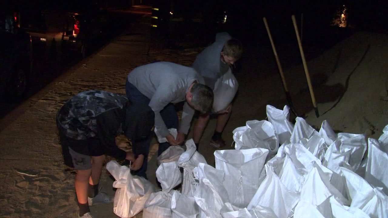 Several people fill sandbags and take them home to prepare for a strong storm system that could cause mudslides in the Woolsey Fire burn area.