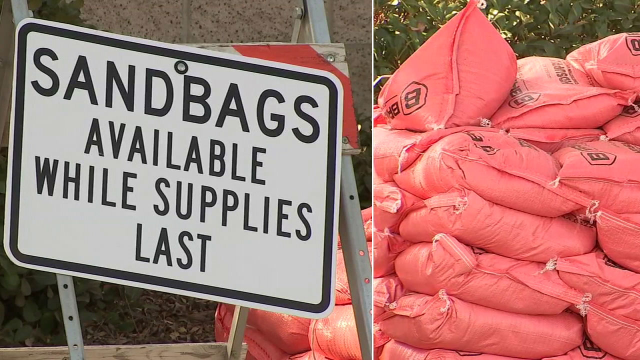 A sign shows sandbags are available while supplies last next to an image of the sandbags available at a station in Ventura County.