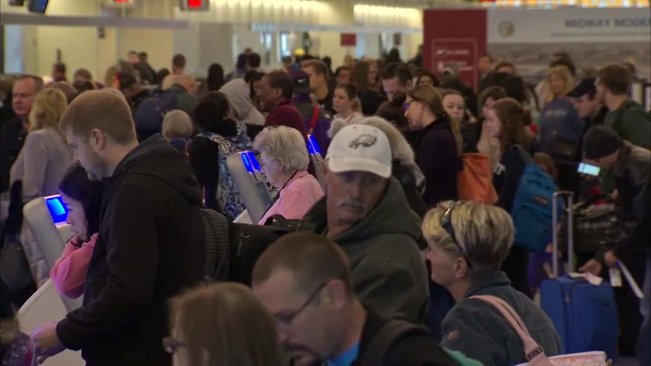 Travelers navigate their way through a crowded airport.
