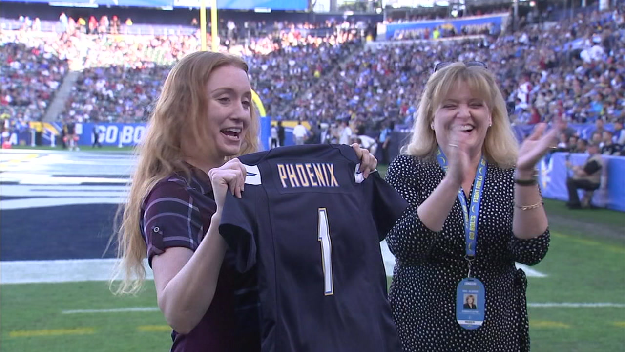 Jess Phoenix holds her personalized Los Angeles Chargers jersey as she is honored for her courage to save horses in the Woolsey Fire.