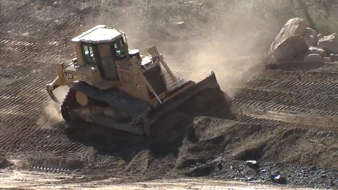 A bulldozer moves dirt on hillsides that were burned by the Holy Fire as a way to prepare communities for any debris or mudflows from the oncoming rainstorm.
