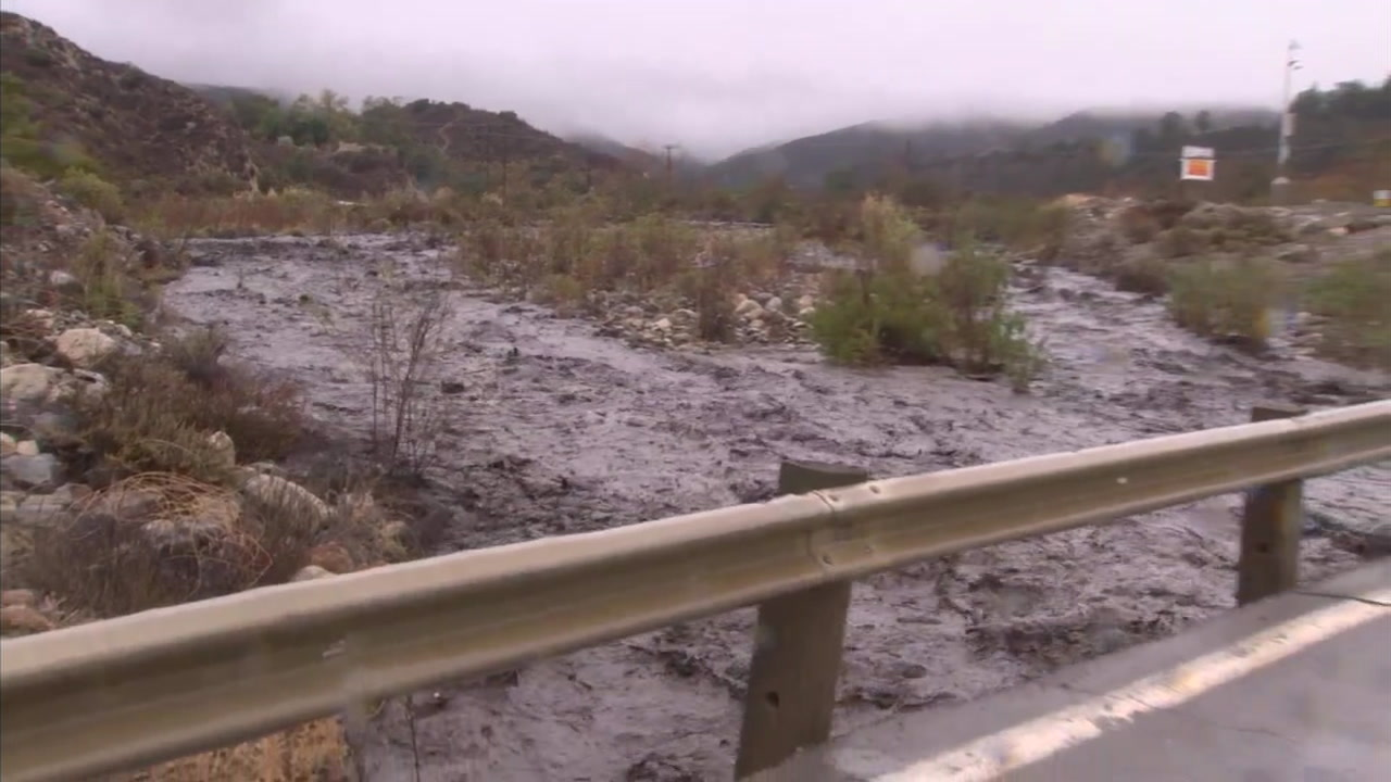 A mixture of mud and debris flows down a swollen Trabuco Creek on Thursday, Nov. 29, 2018.