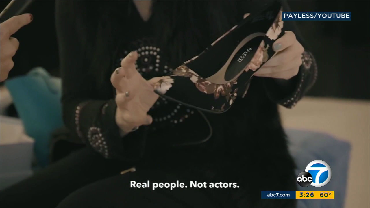 A woman holds a pair of Payless shoes she thought were a designer brand.
